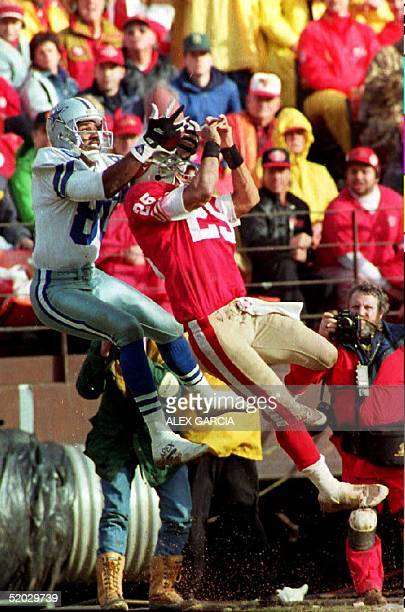 Dallas Cowboys Alvin Harper hauls in a 3rd quarter pass 17 January 1993 as San Francisco 49er's defensive back Eric Davis also goes for the ball...