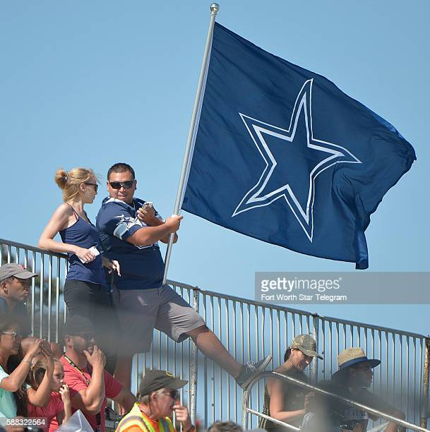 Dallas Cowboys fans bring their blue and white Cowboys Star flag during the afternoon practice at the team's training camp in Oxnard Calif on...