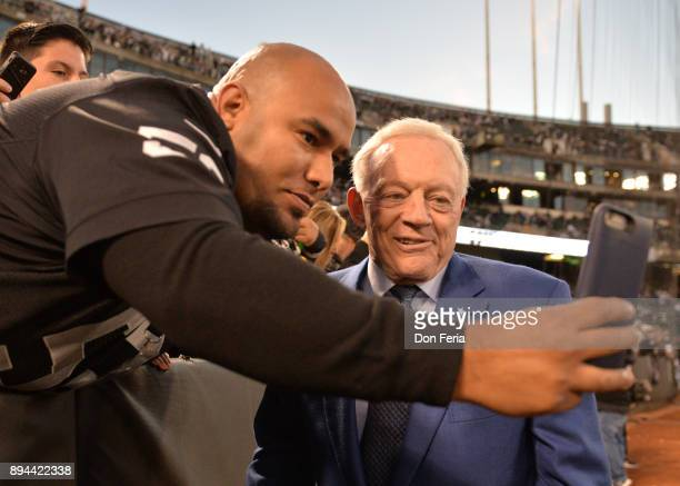 Dallas Cowboys owner Jerry Jones takes a photo with a fan in the stands prior to their game against the Oakland Raiders during their NFL game at...