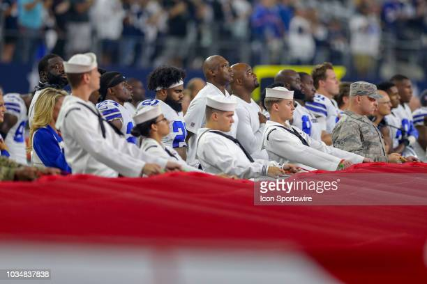 Dallas Cowboys players and coaches stand with military members for the playing of the National Anthem prior to the game between the New York Giants...