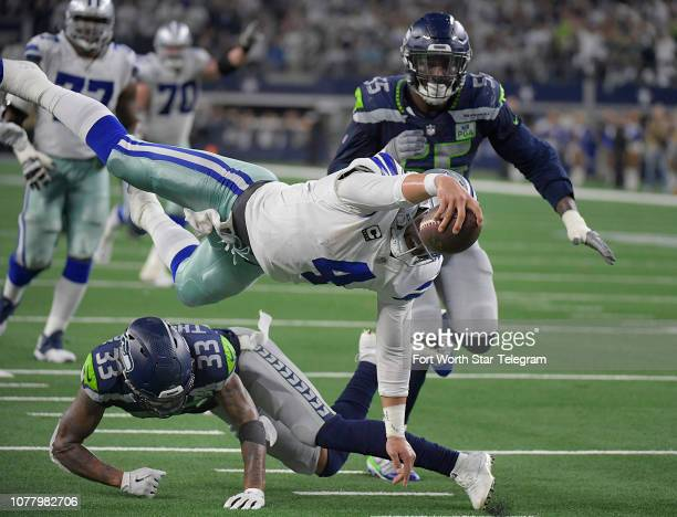 Dallas Cowboys quarterback Dak Prescott dives over Seattle Seahawks safety Tedric Thompson to get the ball down to the 1-yard line during the fourth...