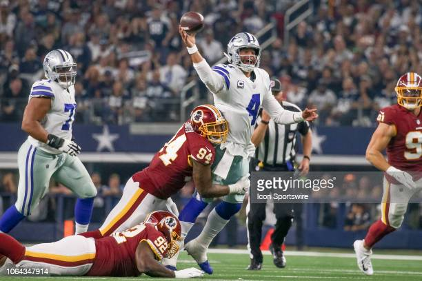 Dallas Cowboys Quarterback Dak Prescott makes a pass while being hit by Washington Redskins Linebacker Preston Smith during the Thanksgiving Day game...