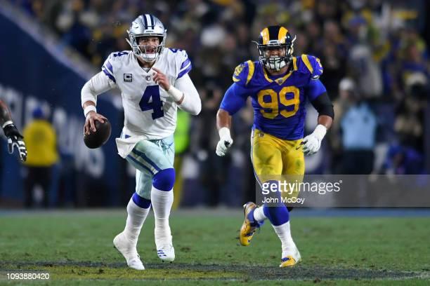 Dallas Cowboys quarterback Dak Prescott runs from Los Angeles Rams defensive end Aaron Donald at Los Angeles Memorial Coliseum on January 12, 2019 in...