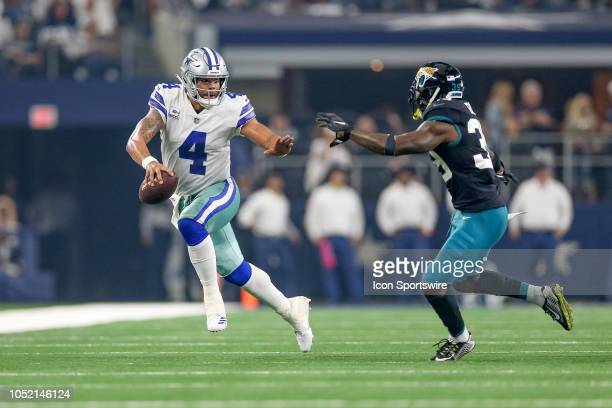Dallas Cowboys quarterback Dak Prescott runs with Jacksonville Jaguars free safety Tashaun Gipson closing during the game between the Jacksonville...