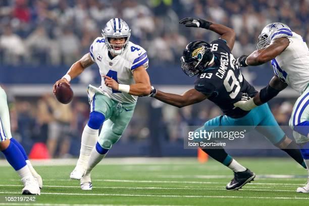 Dallas Cowboys quarterback Dak Prescott scrambles away from pressure by Jacksonville Jaguars defensive end Calais Campbell during the game between...