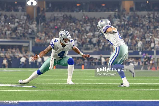 Dallas Cowboys quarterback Dak Prescott slaps hands with wide receiver Cole Beasley after the two connect for a late first half touchdown during the...