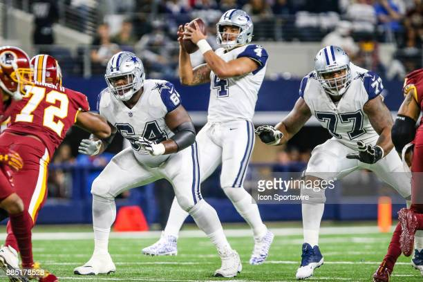 Dallas Cowboys quarterback Dak Prescott takes the snap from center as guard Jonathan Cooper and offensive tackle Tyron Smith look to block during the...