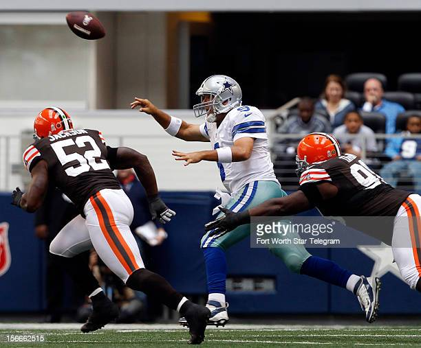 Dallas Cowboys quarterback Tony Romo passes the ball under pressure from Cleveland Browns middle linebacker D'Qwell Jackson and defensive tackle...