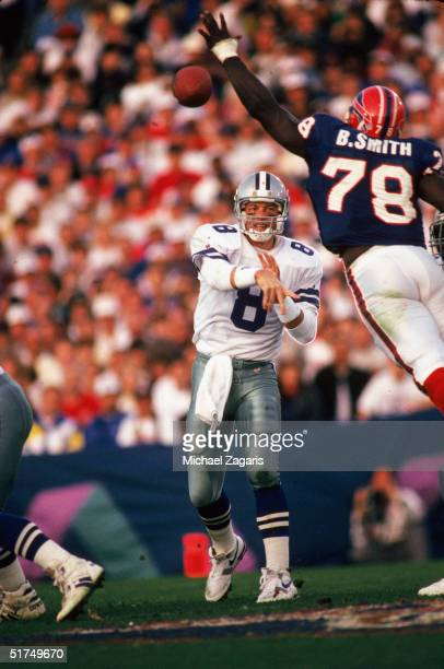 Dallas Cowboys quarterback Troy Aikman passes around leaping Buffalo Bills defensive end Bruce Smith in the second quarter of Super Bowl XXVII on...
