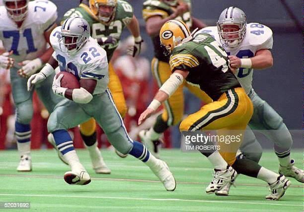 Dallas Cowboys running back Emmitt Smith cuts around teammate Daryl Johnston as Johnston makes a block on Green Bay Packers safety Mike Prior during...