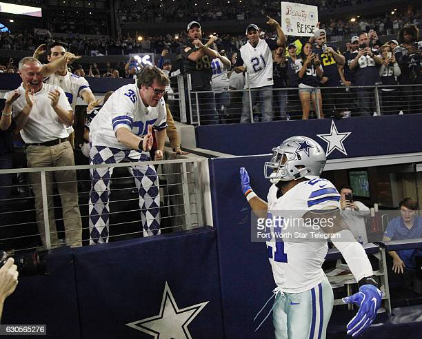 Dallas Cowboys running back Ezekiel Elliott celebrates with a fan in the stands after scoring a first half touchdown against the Detroit Lions Monday...