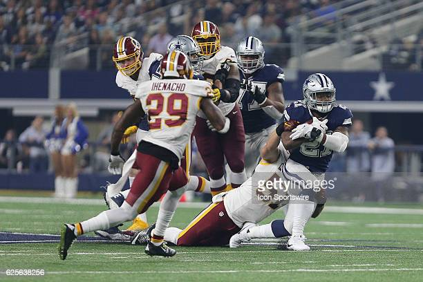 Dallas Cowboys running back Ezekiel Elliott gets dragged down by Washington Redskins inside linebacker Will Compton during the NFL game between the...