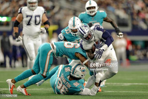 Dallas Cowboys running back Ezekiel Elliott gets tackled by Miami Dolphins defensive back Steven Parker and defensive end Taco Charlton during the...