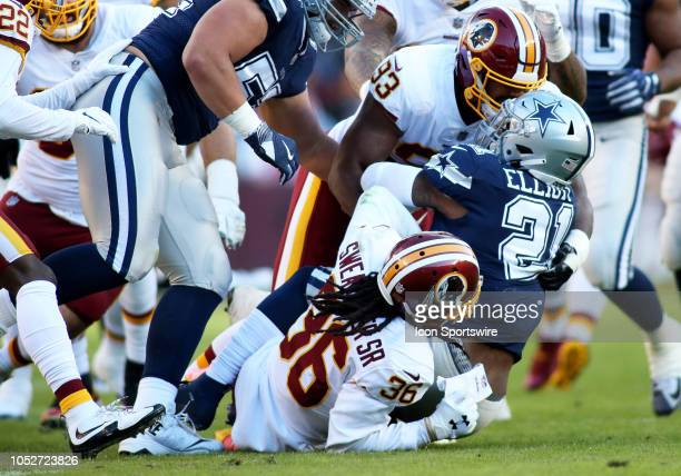 Dallas Cowboys running back Ezekiel Elliott gets taken down by Washington Redskins defensive end Jonathan Allen and Washington Redskins free safety...