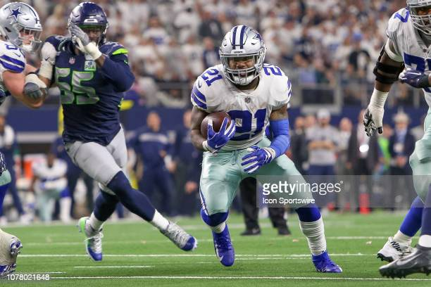 Dallas Cowboys running back Ezekiel Elliott rushes the ball through a hole in the line during the NFC wildcard playoff game between the Seattle...