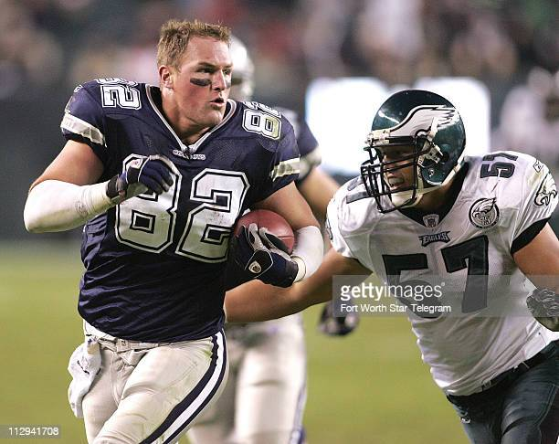Dallas Cowboys tight end Jason Witten looses his helmet and runs after he takes a hit from the Philadelphia Eagles' Quintin Mikell and William James...