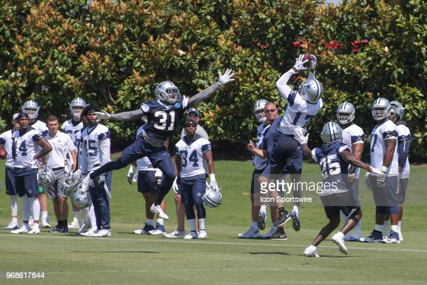 Dallas Cowboys wide receiver Allen Hurns makes a catch between defenders Byron Jones and Xavier Woods during the Dallas Cowboys OTA's on June 6, 2018...