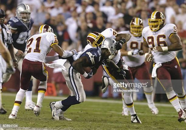 Dallas Cowboys wide receiver Antonio Bryant battles a helmet tackle by the Washington Redskins at FedEx Field, September 27, 2004 in Landover,...