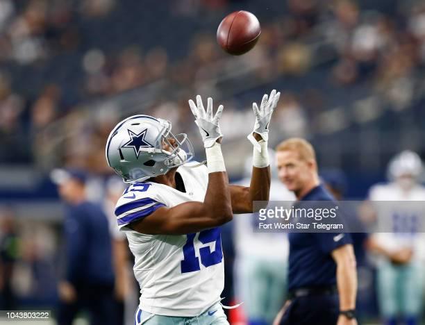 Dallas Cowboys wide receiver Brice Butler catches a pass during team warmups as head coach Jason Garrett watches before a game against the Detroit...