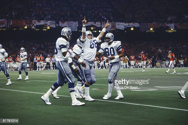 Dallas Cowboys wide receiver Butch Johnson gestures to the crowd and is congratulated by his teammates on the field after scoring against the Denver...