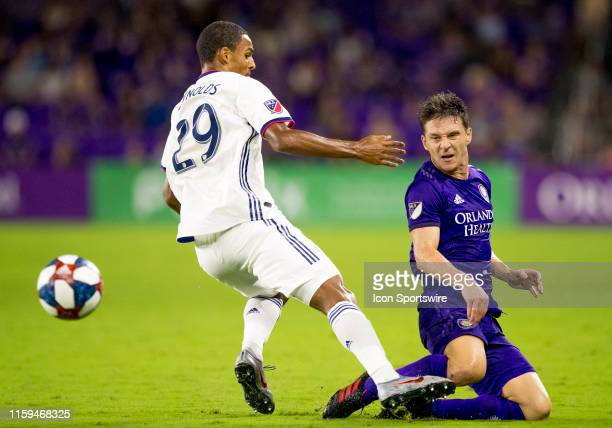 Dallas forward Bryan Reynolds joules Orlando City midfielder Will Johnson during the MLS soccer match between the Orlando City SC and FC Dallas on...
