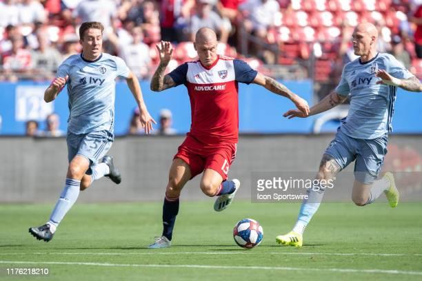 Dallas forward Zdenek Ondrasek dribbles the ball as Sporting Kansas City defenders Matt Besler and Botond Barath close in during the MLS soccer game...