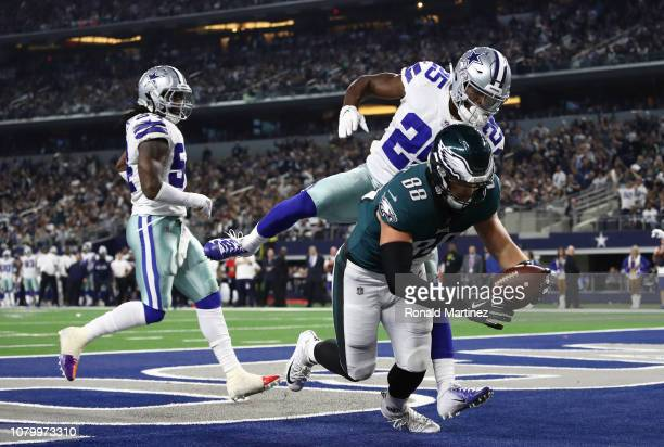Dallas Goedert of the Philadelphia Eagles scores a touchdown against Xavier Woods of the Dallas Cowboys in the fourth quarter at AT&T Stadium on...