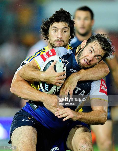Dallas Johnson of the Cowboys is tackled by Nathan Hindmarsh of the Eels during the round three NRL match between the North Queensland Cowboys and...