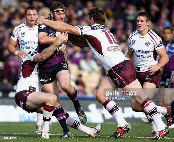 Dallas Johnson of the Storm is tackled by Josh Perry of the Sea Eagles during the round 24 NRL match between the Melbourne Storm and the Manly...