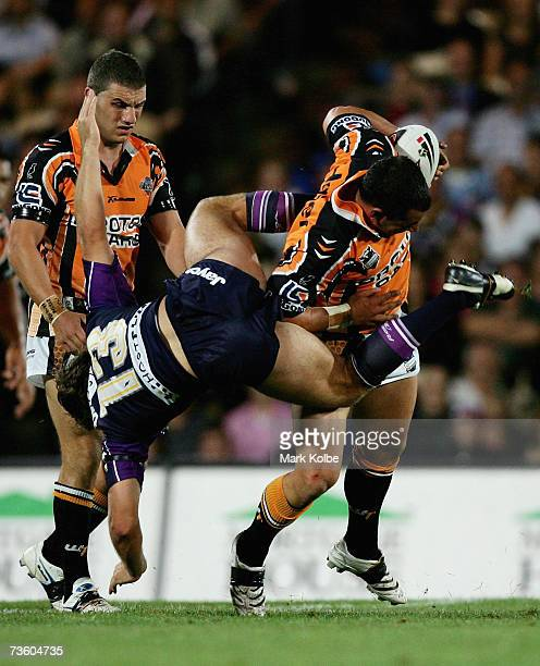 Dallas Johnson of the Storm is upended as he tackles Ben Galea of the West Tigers during the round one NRL match between the Melbourne Storm and the...