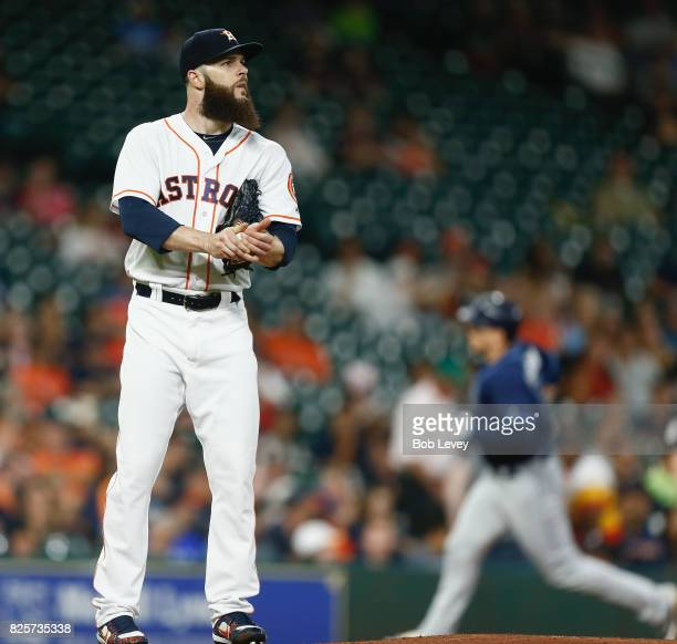 Dallas Keuchel of the Houston Astros rubs the ball as Logan Morrison of the Tampa Bay Rays rounds the bases after hitting a tworun home run in the...