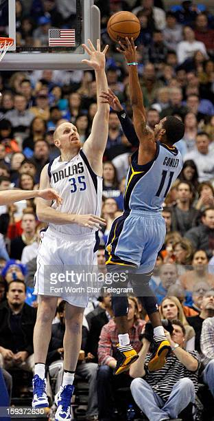 Dallas Mavericks center Chris Kaman tries to block a shot by Memphis Grizzlies point guard Mike Conley during the second quarter at the American...