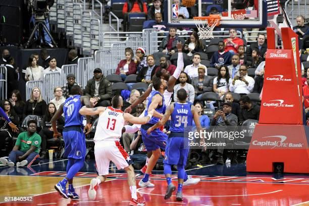 Dallas Mavericks center Salah Mejri fouls Washington Wizards guard John Wall in the first half on November 7 2017 at the Capital One Arena in...