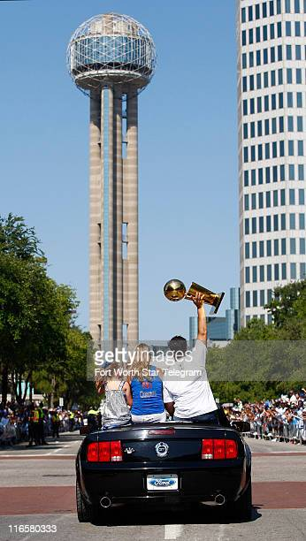 Dallas Mavericks owner Mark Cuban hoists the NBA Championship trophy high as he approaches Reunion Tower in the Dallas Mavericks' parade in Dallas...