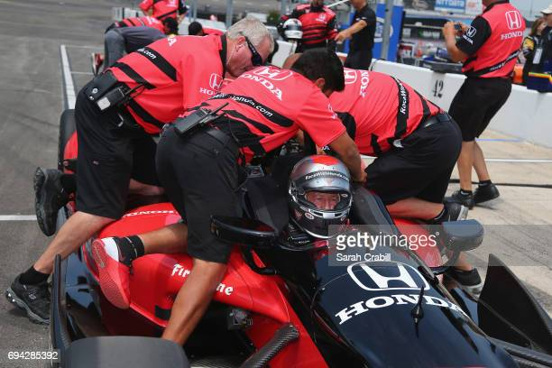 Dallas Mavericks point guard Yogi Ferrell is secured for a ride in a twoseat IndyCar with racing legend Mario Andretti following practice for the...