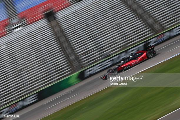 Dallas Mavericks point guard Yogi Ferrell rides in a twoseat IndyCar with racing legend Mario Andretti following practice for the Verizon IndyCar...