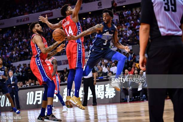 Dallas Mavericks' US guard Daryl Macon throws back the ball past Philadelphia 76ers' US guard Anthony Brown during the preseason NBA basketball game...