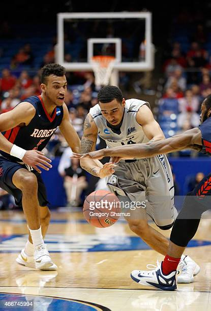 Dallas Moore of the North Florida Ospreys drives to the basket as Elijah Minnie of the Robert Morris Colonials defends during the first round of the...
