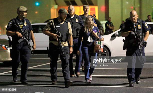 Dallas police officers escort a woman near the scene where eleven Dallas police officers were shot and five have now died on July 8 2016 in Dallas...