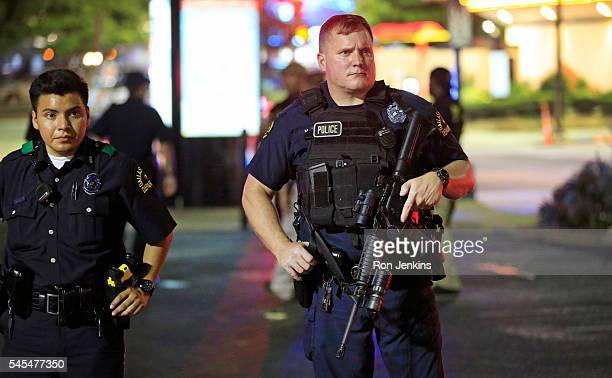 Dallas police stand near the scene where four Dallas police officers were shot and killed on July 7 2016 in Dallas Texas According to reports shots...