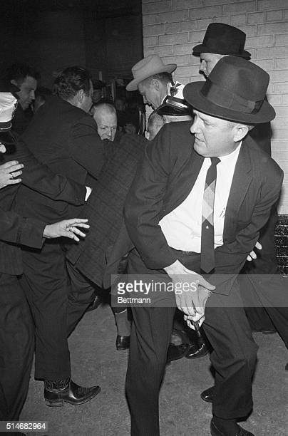 Dallas police struggle with Jack Ruby after the nightclub owner shot alleged assassin Lee Harvey Oswald The officer in the foreground holds the gun...