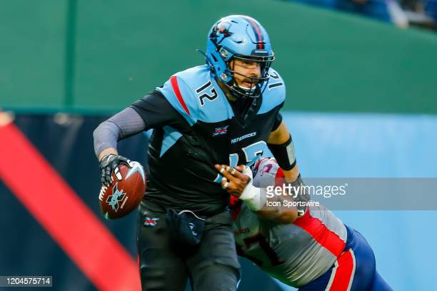 Dallas Renegades quarterback Landry Jones tries to evade Houston Roughnecks defensive lineman Gabe Wright for a sack during the game between the...