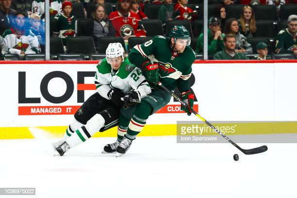 Dallas Stars center Roope Hintz left and Minnesota Wild defenseman Carson Soucy fight for the puck during the preseason game between the Dallas Stars...