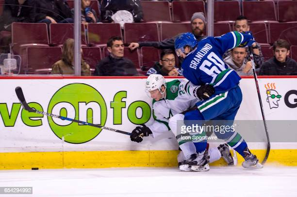 Dallas Stars Defenceman Esa Lindell is checked by Vancouver Canucks Left Wing Markus Granlund during their NHL game at Rogers Arena on March 16, 2017...
