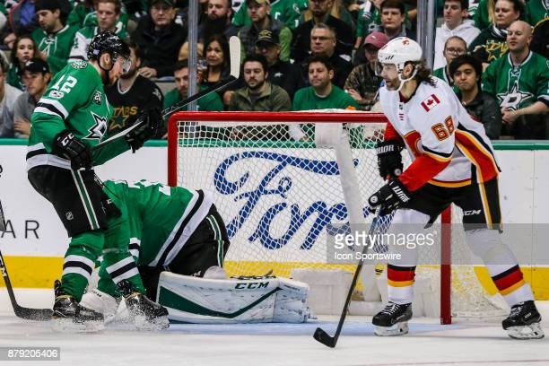 Dallas Stars goalie Ben Bishop covers up the puck as Calgary Flames right wing Jaromir Jagr skates around the net during the game between the Dallas...