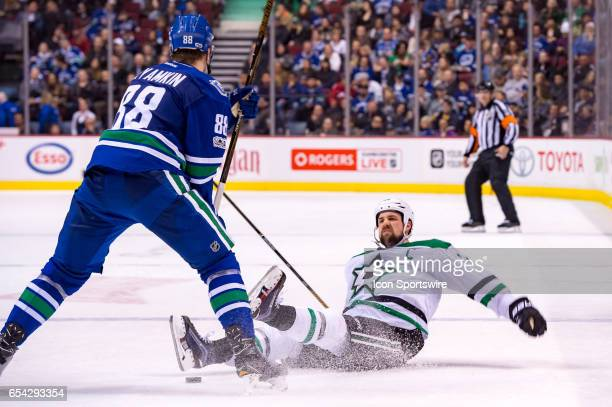 Dallas Stars Left Wing Jamie Benn is checked to the ice by Vancouver Canucks Defenceman Nikita Tryamkin during their NHL game at Rogers Arena on...