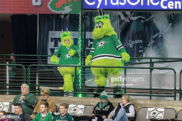 Dallas Stars mascot Victor E Green and his 'minime' entertain the crowd during the NHL game between the Minnesota Wild and Dallas Stars on November...