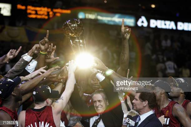 Dallas, UNITED STATES: Light is reflected off the Larry O'Brian trophy as Miami Heat head coach Pat Riley and the Heat celebrate winning Game Six of...