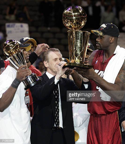 Dallas, UNITED STATES: Miami Heat head coach Pat Riley holds the Larry O'Brian trophy with Dwyane Wade and Shaquille O'Neal after winning the NBA...