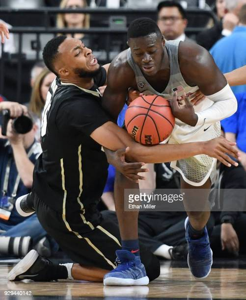 Dallas Walton of the Colorado Buffaloes and Rawle Alkins of the Arizona Wildcats go after a loose ball during a quarterfinal game of the Pac12...
